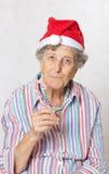 Dame âgée dans le chapeau d'un père noël Image stock