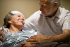 Dame âgée dans le lit menteur de douleur Image libre de droits