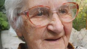 Dame âgée dans les verres semblant en avant et le sourire Portrait de mamie heureuse dans des lunettes passant le temps extérieur clips vidéos