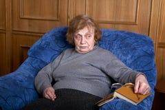 Dame âgée dans un fauteuil et le livre Photographie stock libre de droits