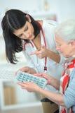 Dame âgée de aide d'infirmière avec la boîte de pilule Images stock
