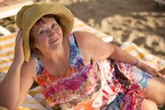 Dame âgée de sourire à la plage sur le lit pliant photographie stock libre de droits