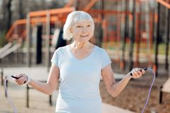 Dame âgée de sourire sautant sa corde Photographie stock libre de droits