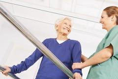 Dame âgée en physiothérapie sur un tapis roulant Photo libre de droits