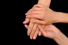 Dame âgée et jeune femme tenant des mains ensemble photographie stock