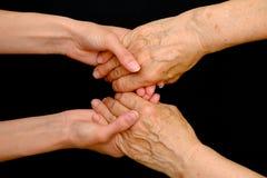 Dame âgée et jeune femme tenant des mains ensemble photos stock