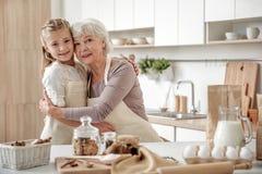 Dame âgée et la petite-fille joyeuses sont prêtes à cuisiner ensemble Photos stock