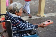 Dame âgée ethnique s'asseyant sur le fauteuil roulant tenant le boîte-cadeau de Noël priant pour l'aumône à la vieille cour d'égl photos stock