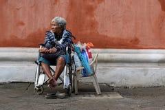 Dame âgée ethnique s'asseyant sur le fauteuil roulant tenant le boîte-cadeau de Noël priant pour l'aumône à la vieille cour d'égl images libres de droits