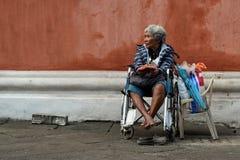 Dame âgée ethnique s'asseyant sur le fauteuil roulant tenant le boîte-cadeau de Noël priant pour l'aumône à la vieille cour d'égl photo libre de droits