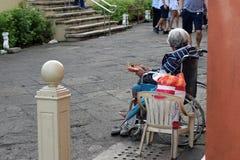 Dame âgée ethnique s'asseyant sur le fauteuil roulant tenant le boîte-cadeau de Noël priant pour l'aumône photos libres de droits