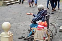 Dame âgée ethnique s'asseyant sur le fauteuil roulant tenant le boîte-cadeau de Noël priant pour l'aumône image stock