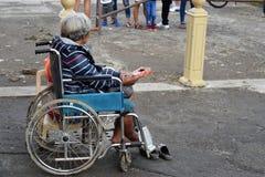 Dame âgée ethnique s'asseyant sur le fauteuil roulant tenant le boîte-cadeau de Noël priant pour l'aumône photo libre de droits