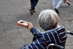 Dame âgée ethnique s'asseyant sur le fauteuil roulant tenant le boîte-cadeau de Noël priant pour l'aumône image libre de droits