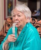 Dame âgée faisant une inhalation Photos stock