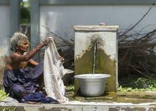 Dame âgée fait la blanchisserie à la pompe communale Images libres de droits