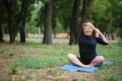 Dame âgée fantastique sur une formation de yoga sur un fond d'extérieur Sport pour chacun concept Copiez l'espace Photographie stock