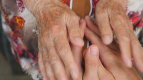 Dame âgée frottant de jeunes mains masculines Petit-fils et grand-mère passant le temps ensemble Soins et concept affectueux fin banque de vidéos