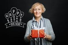 Dame âgée gaie souriant tout en tenant un cadeau d'anniversaire Photographie stock libre de droits