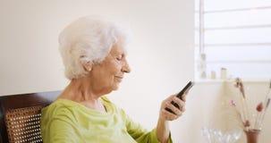 Dame âgée heureuse à l'aide du téléphone portable pour des loisirs Image stock