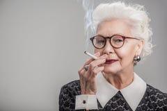 Dame âgée heureuse appréciant le ciggy Photo libre de droits