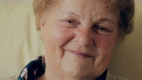 Dame âgée heureuse avec des lunettes souriant et regardant l'appareil-photo banque de vidéos