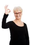 Dame âgée heureuse en verres d'oeil montrant CORRECT. Photos libres de droits