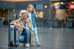 Dame âgée joyeuse et la petite fille posent dans le hall de attente Photo stock
