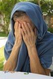 Dame âgée la cache des larmes en ayant couvert son visage de Photo stock