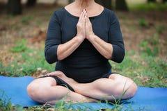 Dame âgée méditante en gros plan sur un fond de jardin Concept de zen et de méditation Image stock