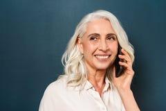 Dame âgée mûre gaie parlant par le téléphone portable Photographie stock