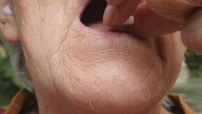 Dame âgée mettant les pilules blanches dans sa bouche Grand-mère prenant les comprimés qui allègent ses problèmes de santé soins  banque de vidéos