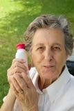 Dame âgée montre le produit qu'elle est satisfaite de Image libre de droits