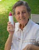 Dame âgée montre le produit se reposant dans le jardin Photographie stock libre de droits