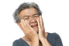 Dame âgée ont le mal de dents sur le blanc photographie stock
