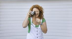 Dame âgée par milieu gai employant l'appareil-photo de vintage Jour, extérieur Femme rouge heureuse de cheveux prenant la photo s Photo libre de droits