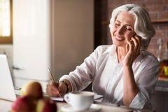 Dame âgée parlant au téléphone tout en prenant des notes Image stock