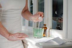 Dame âgée prenant des médicaments délivrés sur ordonnance et le boire Photo libre de droits
