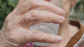 Dame âgée prenant les pilules et le verre à boire de l'eau Grand-mère mettant le comprimé dans sa bouche blanc médical d'isolemen banque de vidéos