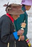 Dame âgée priant avec le petit pain de prière à Lhasa Images libres de droits