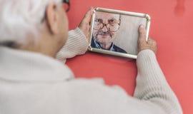 Dame âgée regardant sa photo de mari Image stock