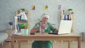 Dame âgée regarde des informations d'ordinateur portable sur des pilules se reposant à une table clips vidéos