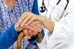 Dame âgée reposant côte à côte se tenir de mains de docteur Images stock