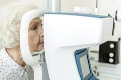 Dame âgée sérieuse s'asseyant près de l'appareil optique photo libre de droits