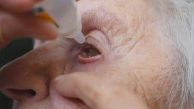Dame âgée s'égouttant des baisses médicales dans son oeil Portrait de grand-mère Soins de santé et concept médical Fermez-vous ve banque de vidéos