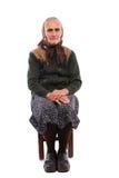 Dame âgée s'asseyant sur la présidence Photo libre de droits