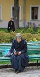 Dame âgée s'asseyant sur un banc affichant un livre Images stock