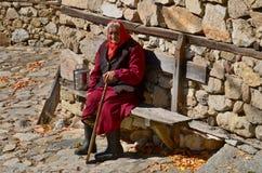 Dame âgée s'asseyent le long du mur en pierre Photographie stock libre de droits