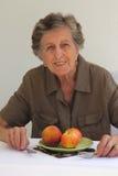 Dame âgée s'assied à la table où il y a un plat avec le fruit Photo stock