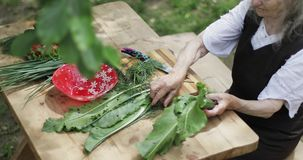 Dame âgée s'assied à une table en bois sur la rue, faisant une salade fraîche des légumes banque de vidéos